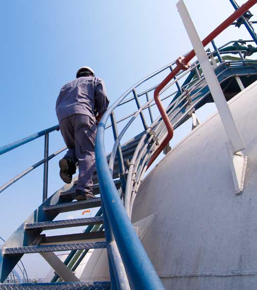 Person climbing manufacturing plant stairs